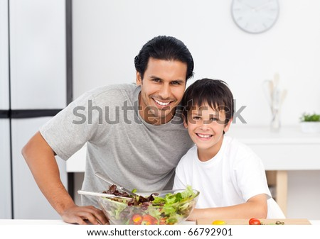 Portrait of a cute boy with his father in the kitchen for lunch