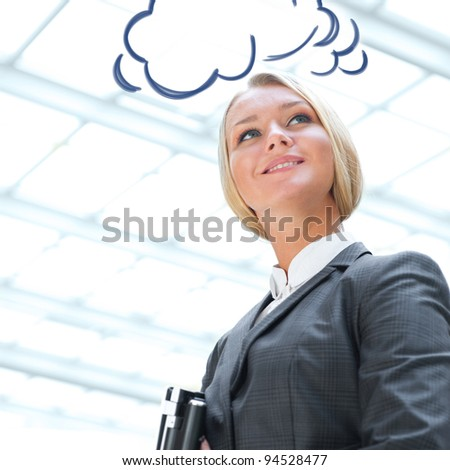 Portrait of a cute business woman with her laptop inside office building. Blank cloud balloon overhead