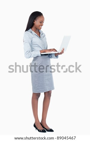 Portrait of a cute businesswoman using a laptop while standing up against a white background