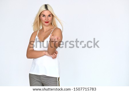 Portrait of a cute caucasian blonde girl with blond hair in a white t-shirt and pants on a white background. It stands right in front of the camera, with emotions in various poses.