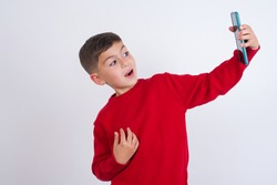 Portrait of a Cute Caucasian kid boy wearing red knitted sweater against white wall  taking a selfie to send it to friends and followers or post it on his social media.