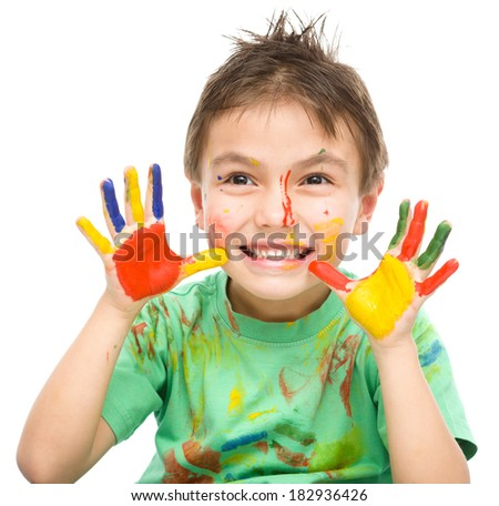 Portrait of a cute cheerful boy showing his hands painted in bright colors, isolated over white