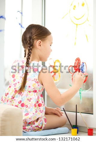 Portrait of a cute cheerful girl playing with paints on window