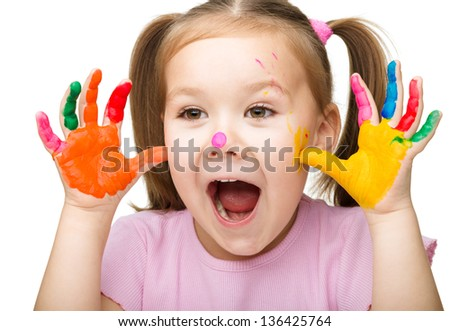 Portrait of a cute cheerful girl showing her hands painted in bright colors, isolated over white