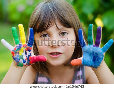 Portrait of a cute cheerful girl with painted hands - stock photo