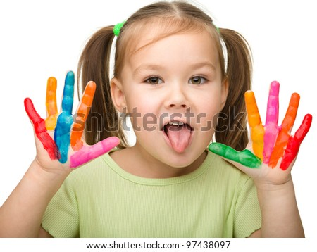 Portrait of a cute cheerful girl with painted hands who is showing her tongue, isolated over white