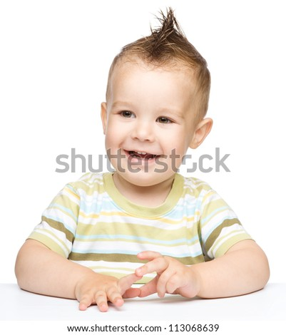 Portrait of a cute cheerful little boy with mohawk hairstyle, who is smiling while sitting at table, isolated over white