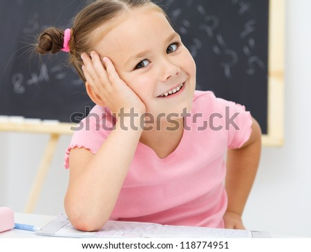 Portrait of a cute cheerful little girl in school