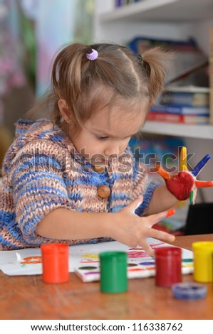 Portrait of a cute child draws paints at the table