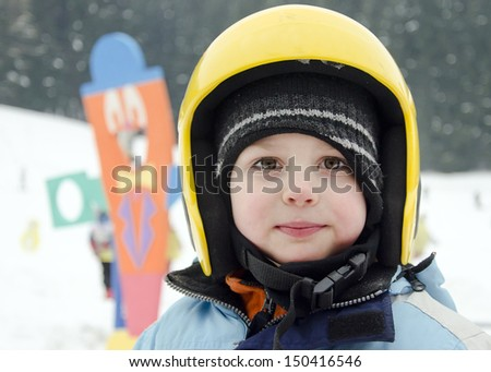 Portrait of a cute child skier, boy or girl, with yellow skiing helmet in a winter ski resort.