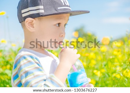 c6b88a4ef0 Portrait of a cute child sucking water from plastic bottle with tube at  flower garden.