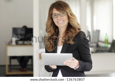 Portrait of a cute confident business woman with digital tablet in office
