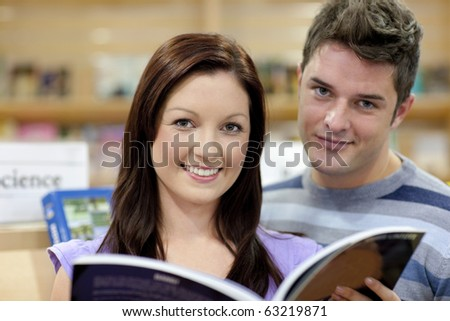 Portrait of a cute couple reading a book in a shop and smiling at the camera
