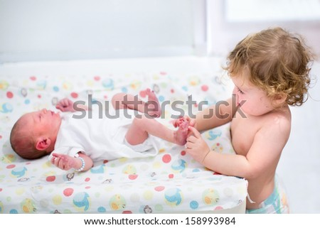 Portrait of a cute curly toddler girl playing with the feet of her newborn baby brother on a changing table