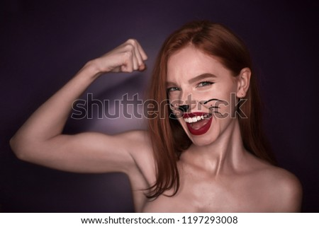 Stock Photo Portrait of a cute excited happy beautiful strong redhead sports girl woman with cat carnival halloween makeup posing isolated over violet purple wall background looking camera showing biceps.