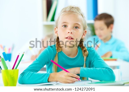 Portrait of a cute girl doing tasks at school