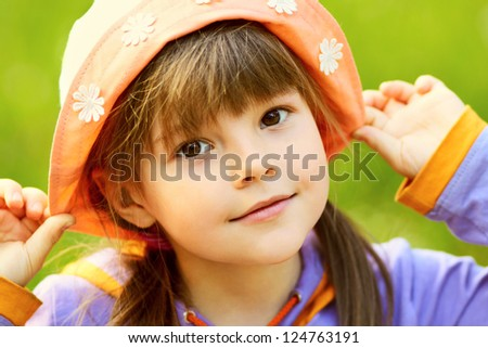 portrait of a cute girl in a hat closeup on a green background