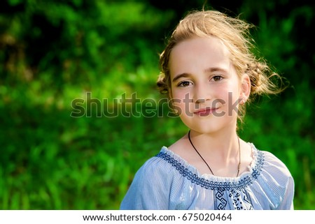 Portrait of a cute girl in a summer park. Sunny day.