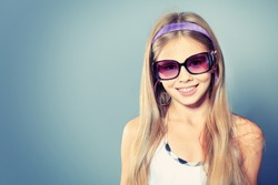 Portrait of a cute girl in sunglasses posing at studio.