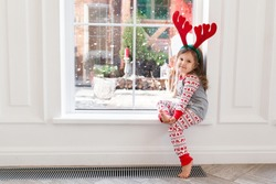 Portrait of a cute girl in xmas pajamas and reindeer antlers sitting at the window during winter. Christmas weekend season with family at home