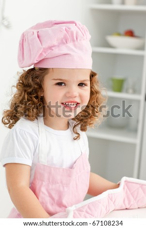 Portrait of a cute girl wearing hat and gloves in the kitchen