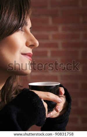 portrait of a cute girl with cup at wall
