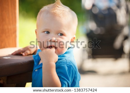 Portrait of a cute handsome boy with a cool haircut on the playground in the park. Rest and early development in the fresh air. #1383757424
