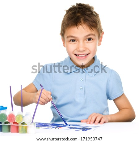 Portrait of a cute happy boy playing with paints, isolated over white