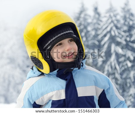 Portrait of a cute happy child skier, boy or girl, with yellow skiing helmet in a winter ski resort.