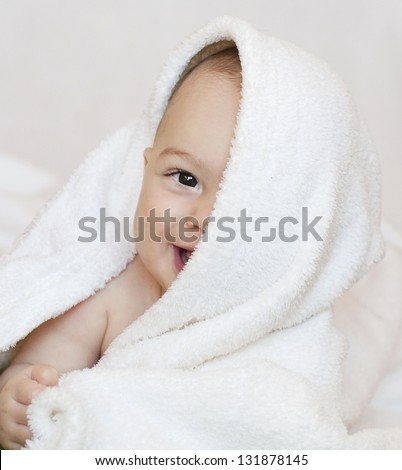 Portrait of a cute happy smiling 6 month old baby, boy or girl, peeking up from a white towel with half of the face covered.