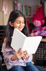 Portrait of a cute Indian school girl sitting on a chair, smiling and reading a diary book surrounded by toys.