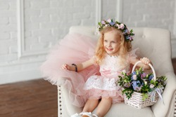 Portrait of a cute kid - girl in a in a pink dress and flower crown. Beautiful little girl in a bright studio sits, lauht and looks out the window and holding a basket of fresh flowers.