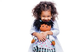 Portrait of a cute little african american girl hugging doll, isolated on white background