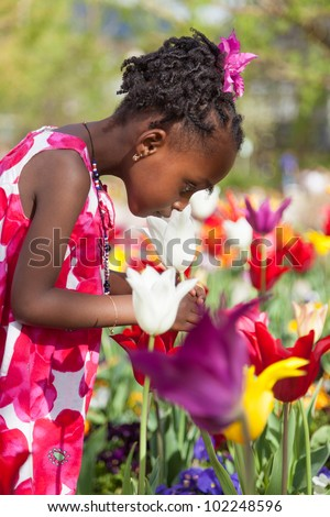 Portrait of a cute little african american girl playing in the garden
