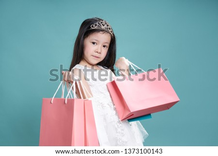 Portrait of a cute little asian girl in white dress hold pink paper shopping bags and looking at camera , isolated on vintage blue color background .