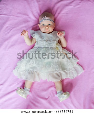 Stock Photo Portrait of a cute little baby girl princess a crown on the head lying pink background