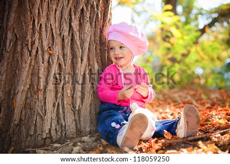 Portrait of a cute little baby posing in autumn park against fallen yellow leaves. Series of photos in my portfolio.