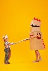 Portrait of a cute little boy in costume of knight with cardboard armour playing with girl in costume of  the cardboard dragon. Childhood dreams. Full length portrait on a yellow background.