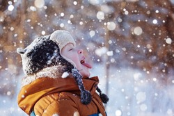 Portrait of a cute little boy in warm clothes who catches snowflakes mouth in winter sunny day