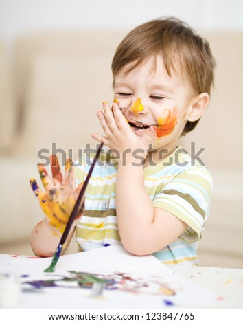 Portrait of a cute little boy messily playing with paints - stock photo