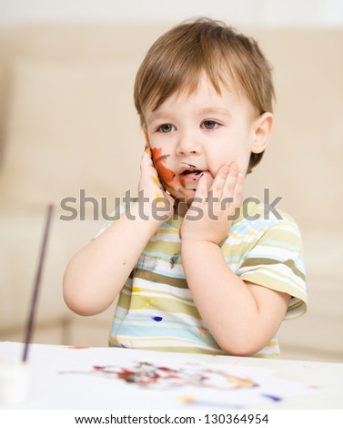 Portrait of a cute little boy messily playing with paints