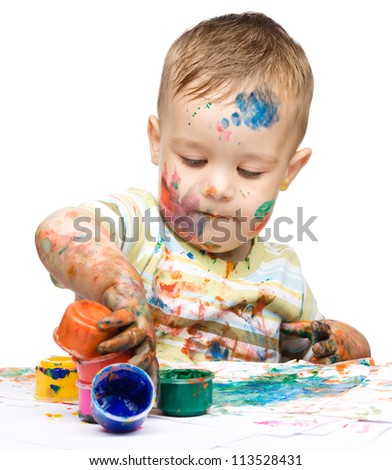 Portrait of a cute little boy messily playing with paints, isolated over white - stock photo