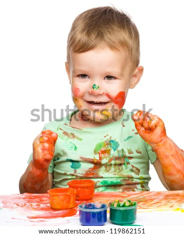 Portrait of a cute little boy playing with paints clenching his fists in joy, isolated over white