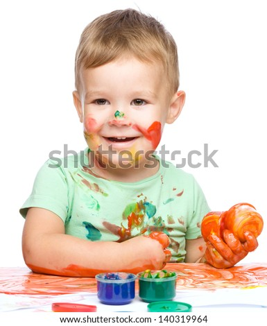 Portrait of a cute little boy playing with paints clenching his fists in joy, isolated over white - stock photo
