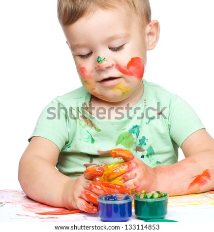 Portrait of a cute little boy playing with paints, isolated over white - stock photo