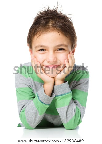 Portrait of a cute little boy sitting at table and supporting his head with hands, isolated over white