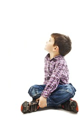 Portrait of a cute little boy sitting on the floor, looking up. Isolated on white background