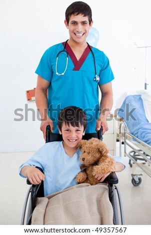 Portrait of a cute little boy sitting on wheelchair and a doctor at the hospital