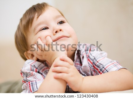 Portrait of a cute little boy supporting his head with hands