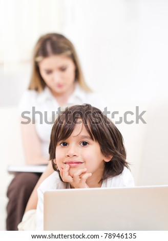 Portrait of a cute little boy using a laptop and smiling - mother in background